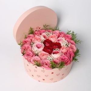 Rooscadeau - Bloemcreatie; Rozentaart in roze giftbox, gevuld met roze en rode rozen. Leuke ronde cadeaubox met hartjes
